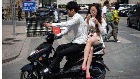 Una pareja de chinos juntos en bici